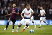 Harry Kane of Tottenham Hotspur runs with the ball under pressure form Sergio Busquets of Barcelona during the Group B match of the UEFA Champions League between Tottenham Hotspur and FC Barcelona at Wembley Stadium on October 3, 2018 in London, United Kingdom.