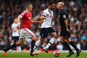Referee Mike Dean evades Dele Alli of Tottenham Hotspur and Morgan Schneiderlin of Manchester United during the Barclays Premier League match between Tottenham Hotspur and Manchester United at White Hart Lane on April 10, 2016 in London, England.