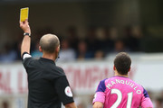 Mike Dean gives Javier Manquillo of Sunderland a yellow card  during the Premier League match between Tottenham Hotspur and Sunderland at White Hart Lane on September 18, 2016 in London, England.
