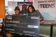 (L-R) $10,000 scholarship winner Bria Gregory, Detroit Lions running back Reggie Bush and Bria's mother attend the Touchdown For Teens Campaign at Taco Bell on August 26, 2014 in Royal Oak, Michigan.