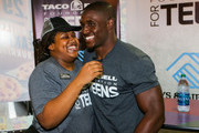 $10,000 scholarship winner Bria Gregory (L) and Detroit Lions running back Reggie Bush attend the Touchdown For Teens Campaign at Taco Bell on August 26, 2014 in Royal Oak, Michigan.
