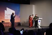Edward Enninful, Editor-in-Chief of British Vogue looks on as  (L-R) Tai Shani, Oscar Murillo Helen Cammock and Lawrence Abu Hamdan celebrate after being announced as the joint winners of Turner Prize 2019 in Margate.