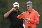 Justin Rose (R) of England talks with caddie Mark Fulcher (L) during a practice round prior to the 2018 U.S. Open at Shinnecock Hills Golf Club on June 13, 2018 in Southampton, New York.