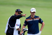 Justin Rose of England looks at a shot with his caddie Mark Fulcher during Round Two of the 113th U.S. Open at Merion Golf Club on June 14, 2013 in Ardmore, Pennsylvania.