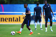 Patrice Evra passes the ball during a France training session on the eve of the UEFA EURO 2016 Final against Portugal at Clairefontaine on July 9, 2016 in Paris, France.