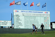 Justin Rose of England and caddie Mark Fulcher walk in front of a leaderboard on the 14th green during the final round of the 2018 U.S. Open at Shinnecock Hills Golf Club on June 17, 2018 in Southampton, New York.