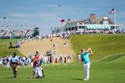 Justin Rose of England plays his second shot on the first hole as caddie Mark Fulcher looks on during the third round of the 2018 U.S. Open at Shinnecock Hills Golf Club on June 16, 2018 in Southampton, New York.