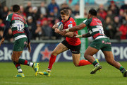 Jacob Stockdale of Ulster takes on Manu Tuilagi (R) and Jordan Olowofela during the Champions Cup match between Ulster Rugby and Leicester Tigers at the Kingspan Stadium on October 13, 2018 in Belfast, United Kingdom.
