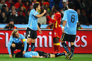 Diego Forlan of Uruguay checks on his team mate Jorge Fucile after he made a hard landing following a high challenge with Samuel Inkoom of Ghana during the 2010 FIFA World Cup South Africa Quarter Final match between Uruguay and Ghana at the Soccer City stadium on July 2, 2010 in Johannesburg, South Africa.