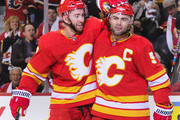T.J. Brodie #7 celebrates with Mark Giordano #5 of the Calgary Flames after Giordano scored the Flames' second goal against the Vancouver Canucks during an NHL game at Scotiabank Saddledome on October 6, 2018 in Calgary, Alberta, Canada.