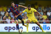 Lionel Messi of Barcelona is tackled by Mateo Pablo Musacchio (R) of Villarreal during the La Liga match between Villarreal CF and FC Barcelona at El Madrigal stadium on August 31, 2014 in Villarreal, Spain.