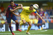 Pedro of Barcelona competes for the ball with Bruno Soriano (R) of Villarreal during the La Liga match between Villarreal CF and FC Barcelona at El Madrigal stadium on August 31, 2014 in Villarreal, Spain.