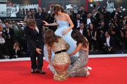 Brady Corbet, Natalie Portman, Stacy Martin help Raffey Cassidy (C) with her shoes on the red carpet ahead of the 'Vox Lux' screening during the 75th Venice Film Festival at Sala Grande on September 4, 2018 in Venice, Italy.