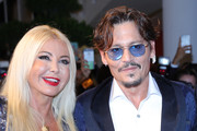 """(L-R) Monika Bacardi and Johnny Depp walk the red carpet ahead of the """"Waiting For The Barbarians"""" screening during the 76th Venice Film Festival at Sala Grande on September 06, 2019 in Venice, Italy."""
