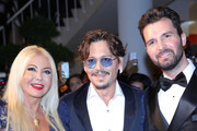 """(L-R) Monika Bacardi, Johnny Depp and Andrea Iervolino walk the red carpet ahead of the """"Waiting For The Barbarians"""" screening during the 76th Venice Film Festival at Sala Grande on September 06, 2019 in Venice, Italy."""