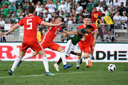 Javier Aquino #20 of Mexico is pushed by Aaron Ramsey #10 of Wales as he attacks the goal during the second half of their friendly international soccer match at the Rose Bowl on May 28, 2018 in Pasadena, California.