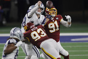 Andy Dalton #14 of the Dallas Cowboys attempts to get a pass off against Jonathan Allen #93 and Ryan Kerrigan #91 of the Washington Football Team during the fourth quarter of a game at AT&T Stadium on November 26, 2020 in Arlington, Texas.