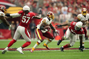 Running back Adrian Peterson #26 of the Washington Redskins runs past linebacker Josh Bynes #57 and defensive tackle Robert Nkemdiche #90 of the Arizona Cardinals during the first quarter at State Farm Stadium on September 9, 2018 in Glendale, Arizona.