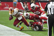 Running back Adrian Peterson #26 of the Washington Redskins is tackled by defensive backs Budda Baker #36, Antoine Bethea #41 and Tre Boston #33 of the Arizona Cardinals during the second quarter at State Farm Stadium on September 9, 2018 in Glendale, Arizona.