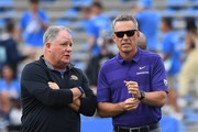 Head coach Chip Kelly of the UCLA Bruins and head coach Chris Petersen of the Washington Huskies look as players warm up for the game on October 6, 2018 in Pasadena, California.