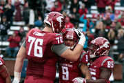 Cody O'Connell #76 and John Thompson #85 of the Washington State Cougars congratulate teammate Gabe Marks #9 after his touchdown against the Washington Huskies in the second half during the 109th Apple Cup at Martin Stadium on November 25, 2016 in Pullman, Washington.  Washington defeated Washington State 45-17.