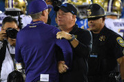 As a University of California Police Officer provides security, head coach Chip Kelly of the UCLA Bruins congratulates head coach Chris Petersen of the Washington Huskies after the game at the Rose Bowl on October 6, 2018 in Pasadena, California.