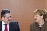 German Chancellor Angela Merkel and German Vice Chancellor, Economy and Energy Minister Sigmar Gabriel look at eachothers at the beginning of the weekly cabinet meeting on January 25, 2017 at the Chancellery in Berlin. / AFP / STEFFI LOOS