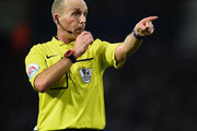 Referee Mike Dean gestures during the Barclays Premier League match between West Bromwich Albion and A.F.C. Bournemouth at The Hawthorns on December 19, 2015 in West Bromwich, England.
