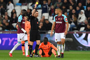 West Ham United's New Zealand defender Winston Reid (R) receives a yellow card during the English Premier League football match between West Ham United and Liverpool at The London Stadium, in east London on November 4, 2017. / AFP PHOTO / Ben STANSALL / RESTRICTED TO EDITORIAL USE. No use with unauthorized audio, video, data, fixture lists, club/league logos or 'live' services. Online in-match use limited to 75 images, no video emulation. No use in betting, games or single club/league/player publications.  /