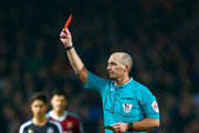 Referee Mike Dean shows Moussa Sissoko of Newcastle United (not pictured) a red card during the Barclays Premier League match between West Ham United and Newcastle United at Boleyn Ground on November 29, 2014 in London, England.