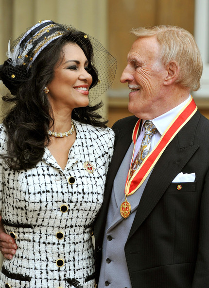 Sir Bruce Forsyth Knighted At Buckingham Palace [bruce forsyth,wilnelia,elizabeth ii,sir,tv presenter,fans,event,outerwear,suit,gesture,formal wear,buckingham palace,england,london,campaigning]