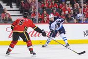 Mark Giordano #5 of the Calgary Flames defends against Blake Wheeler #26 of the Montreal Canadiens during an NHL game at Scotiabank Saddledome on January 20, 2018 in Calgary, Alberta, Canada.