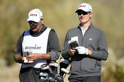 Justin Rose of England (R) looks on with his caddie Mark Fulcher from the 16th hole during the second round of the Accenture Match Play Championship at the Ritz-Carlton Golf Club on February 24, 2011 in Marana, Arizona.