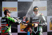 Second placed, Tom Sykes (L) of Great Britain on the Kawasaki ZX-10R for Kawasaki Racing Team, Third placed, Loris Baz (R) of France on the Kawasaki ZX-10R for Kawasaki Racing Team spray first placed, Eugene Laverty (C8) of Ireland on the Aprilia RSV4 for the Aprilia Racing Team on the podium after the World Superbikes Race 2 at TT Circuit Assen on April 28, 2013 in Assen, Netherlands.