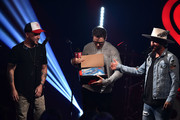 """Chris Lucas and Preston Brust of LoCash present Bobby Bones with a pair of sneakers during iHeartMedia's Bobby Bones Book Release Party - """"FAIL UNTIL YOU DON'T: FIGHT. GRIND. REPEAT."""" on June 19, 2018 in New York City."""