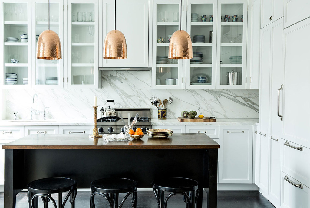 Marble and copper strike subtle yet luxe notes in the Winsteads' open kitchen.   Lonny.com