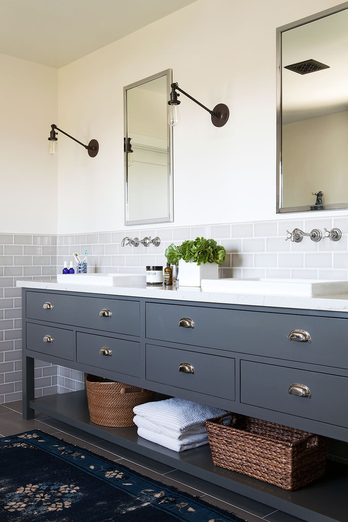A soft blue bathroom vanity is illuminated by armed wall sconces from Schoolhouse Electric Co. | Lonny.com