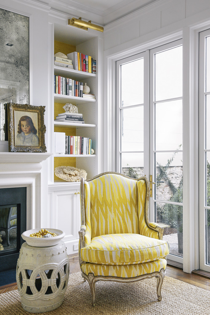 An upholstered chair near a bookshelf with coordinating backsplash | Lonny