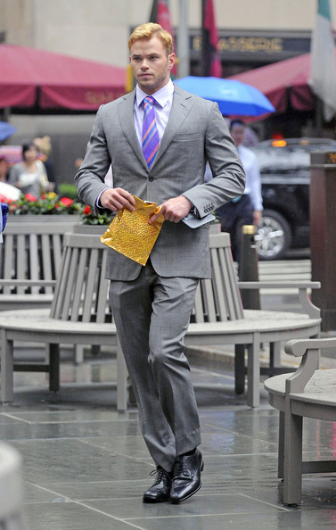 "Kellan Lutz wears a grey suit and purple striped tie while on the New York City set of his upcoming film ""Syrup""."