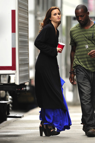 Leighton Meester, wearing a black robe over a blue evening gown dress, walks onto the set of