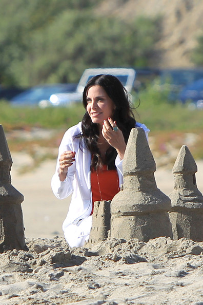 "Courteney Cox and her onscreen son Dan Byrd film a scene together on a beach in Santa Monica for their hit TV series ""Cougar Town"". Cox, dressed in white jeans, a white hoody and red top, built sandcastles, flew a kite and watched the sunset with Byrd."
