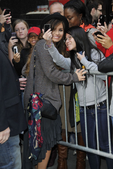"Demi Lovato Singer Demi Lovato poses with fans after her appearance on ""Good Morning America"" wearing a long grey tunic dress."