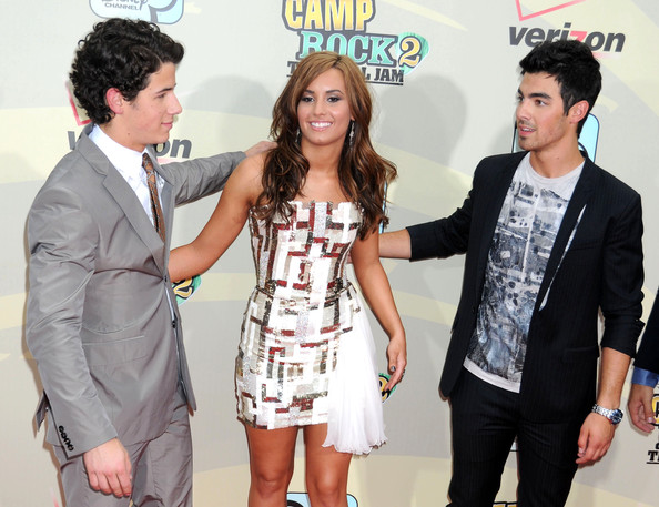 Demi Lovato A slghtly awkward-looking Demi Lovato arrives to pose with ex-boyfriend Joe Jonas (right) and his brother, Nick, at the New York premiere of the Disney movie