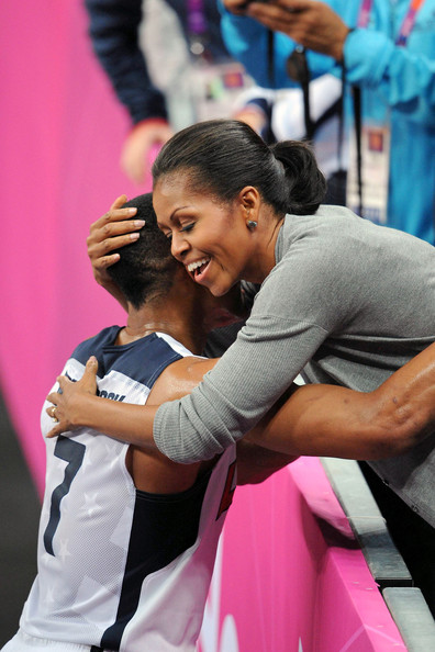 First Lady Michelle Obama gets a few sweaty hugs from the American players after watching the USA Men's Basketball team defeat France during the 2012 Olympic Games.