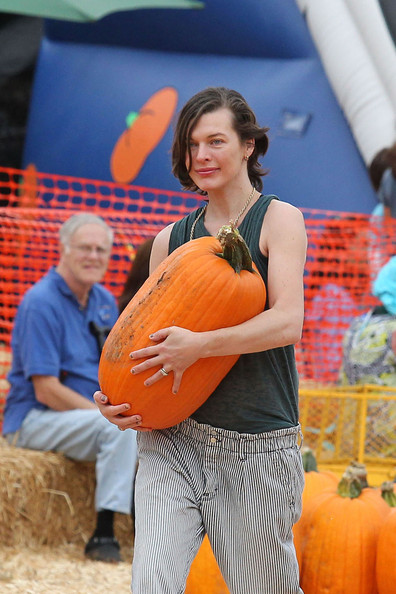 Milla Jovovich prepares for Halloween at the pumpkin patch with husband Paul Anderson and the couples daughter, Ever Anderson, in Los Angeles