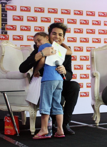 American singer-songwriter Adam Lambert seen meeting a 6 year old fan and receiving a gift while at a press conference at Radio station 94.7 Highveld Stere in Sandton, Johannesburg