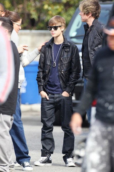"Justin Bieber Justin Bieber looks ready for business as the serious-looking teenybopper prepares to film his latest music video in Los Angeles. The ""Never Say Never"" star received a pep talk from a crew member before making his way onto the set. The teen singer looked hip with his retro glasses, leather jacket, and 'blinged' out silver necklace."