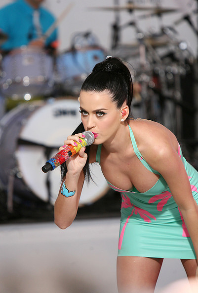 "Katy Perry performs a mini concert in Times Square to launch the new 2011 VW Jetta wearing a palm tree clad PVC dress. Dressed in a skintight dress (with hot pink palm trees) and her hair pulled back into a sleek ponytail, the ""California Gurls"" singer also performed her other two hit songs, ""Hot N Cold"" and ""I Kissed A Girl."" The pop songstress also shows off her new matching tattoo with fiance Russell Brand, seen on the inside of her right arm, ""Anuugacchati Pravaha"" meaning Go With the Flow."