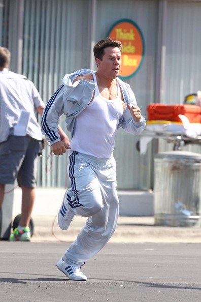 "Mark Wahlberg dashes across the set of ""Pain and Gain"" while shooting an action scene for the upcoming Michael Bay film. Wearing a white tank top and Adidas track suit, Wahlberg can be seen running across a Miami rooftop before taking to the streets."