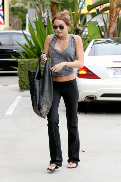 Miley Cyrus rocks a belly shirt and yoga pants as she makes her way to a Pilates class.